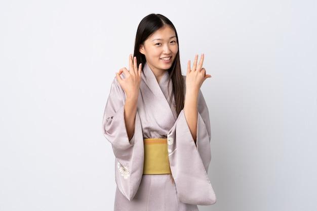 Кимоно молодой китайской девушки нося показывая одобренный знак с двумя руками