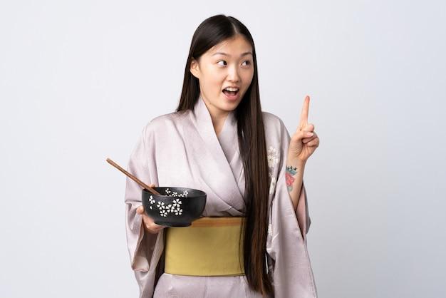 箸で麺のボウルを押しながら指を離しながら解決策を実現しようとする孤立した白の上に着物を着ている中国人少女