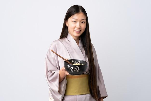箸で麺のボウルを押しながら幸せな表情で孤立した白で着物を着ている中国の少女