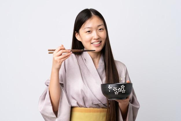 箸で麺のボウルを保持している孤立した白で着物を着ている若い中国人の女の子