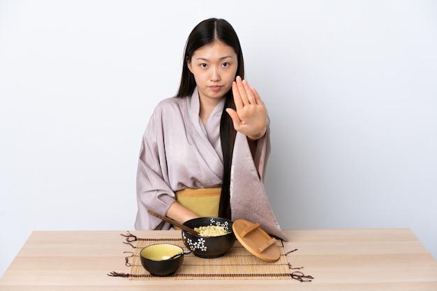 着物を着て麺を食べて停止ジェスチャーを作る中国の少女