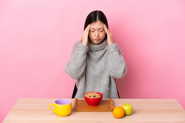 頭痛を持つテーブルで朝食を持っている若い中国の女の子