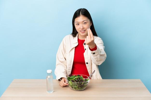 Молодая китайская девушка ест салат, делая деньги жест