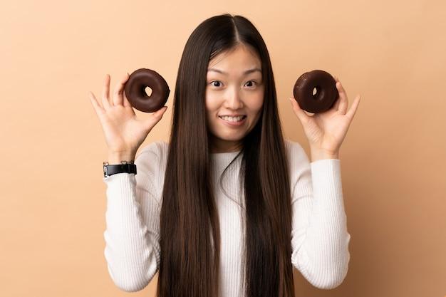 ドーナツを保持している若い中国の女の子
