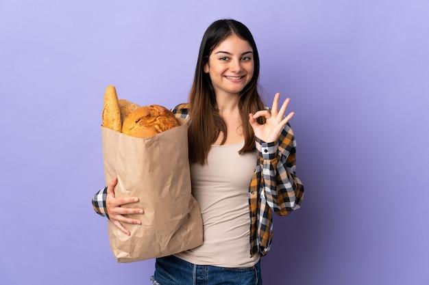 Молодая женщина, держащая мешок, полный хлеба, изолированные на фиолетовый, показывая знак ок с пальцами