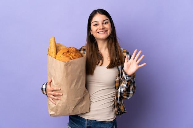 Молодая женщина, держащая мешок, полный хлеба, изолированных на фиолетовый салютов с рукой с счастливым выражением