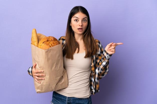 Молодая женщина, держащая мешок, полный хлеба, изолированных на фиолетовый удивлен и указывая пальцем в сторону
