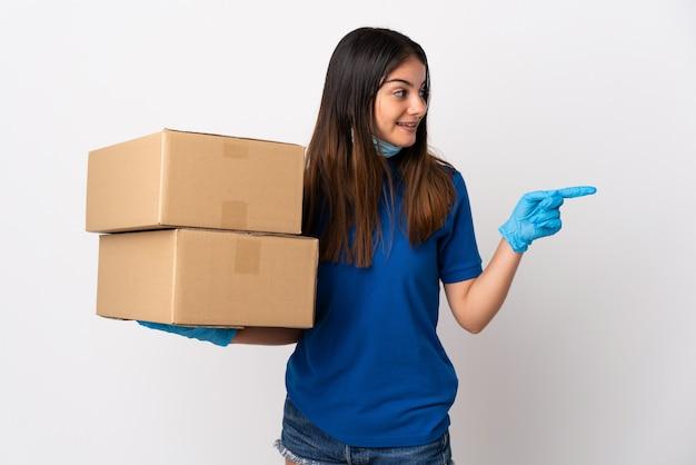 製品を提示する側を指している白で隔離されるマスクでコロナウイルスから保護する若い配達女性