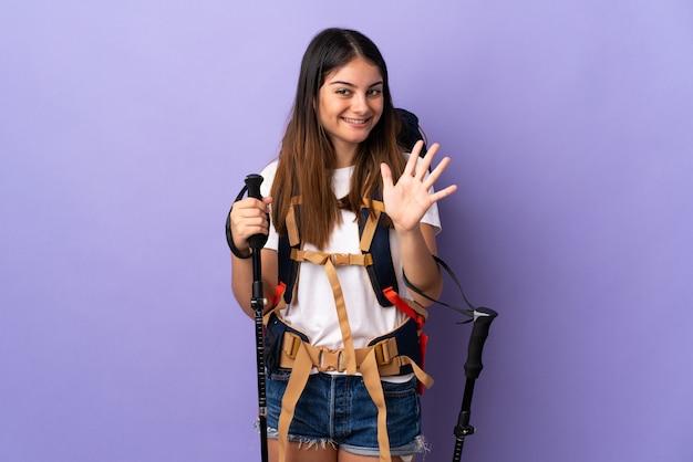 Молодая женщина с рюкзаком и треккинг поляков, изолированные на фиолетовый, считая пять с пальцами