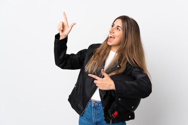 Молодая женщина, держащая мотоциклетный шлем на белом фоне, указывая указательным пальцем отличная идея
