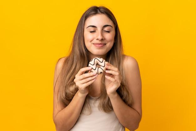 ドーナツを持って孤立した黄色の若い女性