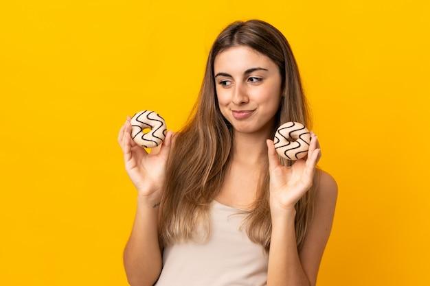 孤立した黄色持株ドーナツの若い女性