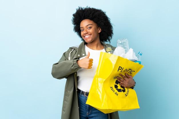 カラフルな親指ジェスチャーを与える上で分離されてリサイクルバッグを保持している若いアフリカ系アメリカ人女性
