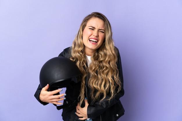 Молодая бразильская женщина, держащая мотоциклетный шлем, изолирована на фиолетовый, много улыбается