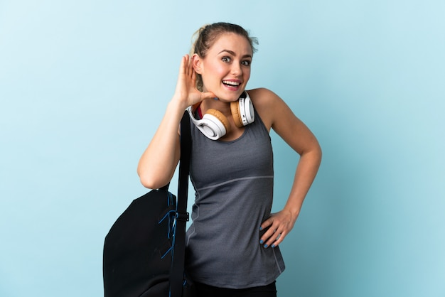耳に手を置くことによって何かを聞いて青に分離されたスポーツバッグを持つ若いスポーツブラジルの女性