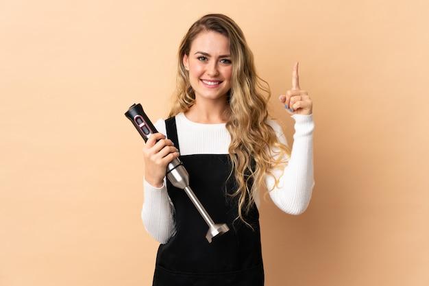 Молодая бразильская женщина, используя ручной блендер, изолированные на бежевом, показывая и поднимая палец в знак лучших