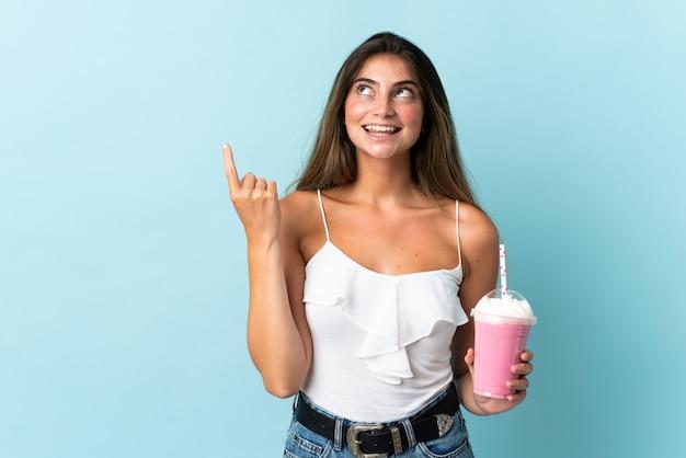 Молодая женщина с клубничный молочный коктейль, изолированных на синем, указывая отличная идея