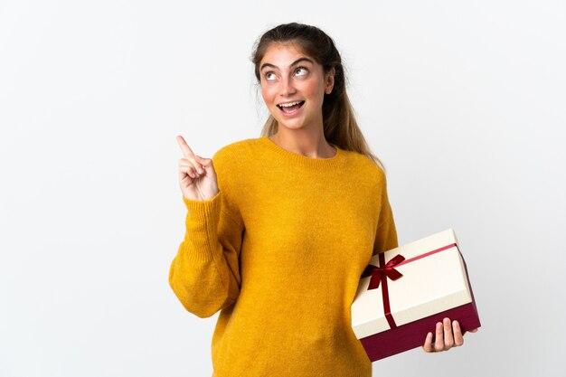 指を持ち上げながら解決策を実現するために白で隔離される贈り物を保持している若い女性
