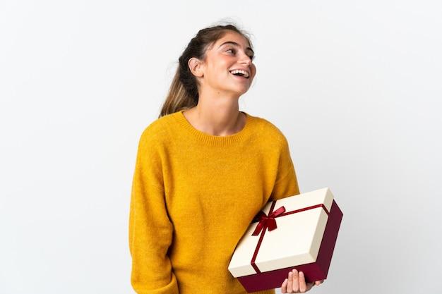 Молодая женщина, держащая подарок, изолированные на белый смех