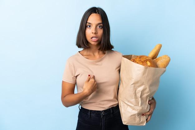 Молодая латинская женщина покупая некоторые хлебы изолированные на сини указывая к себе