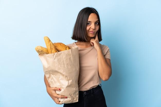 Молодая латинская женщина покупая некоторые хлебы изолированные на сини и думать