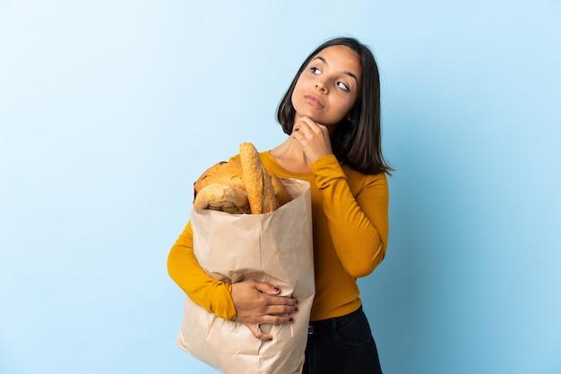 Молодая латинская женщина покупая некоторые хлебы изолированные на сини имея сомнения