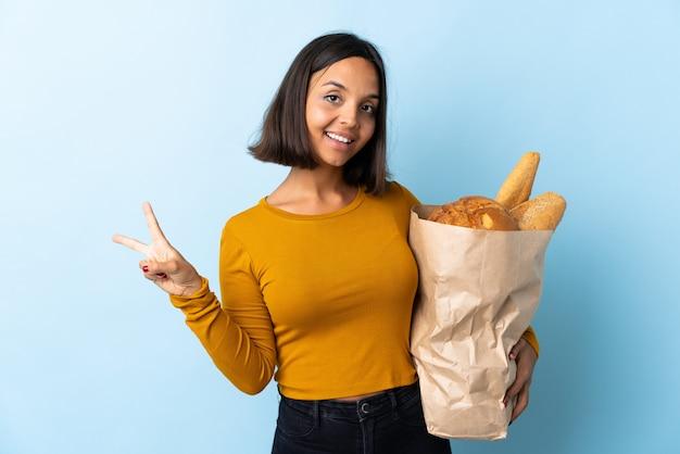 Молодая латинская женщина покупая некоторые хлебы изолированные на сини усмехаясь и показывая знак победы