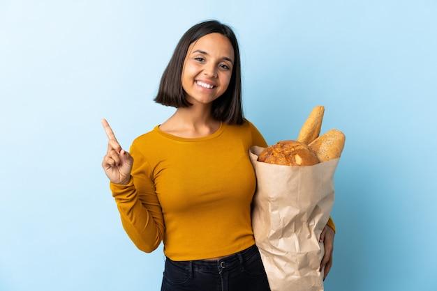 Молодая латинская женщина покупая некоторые изолированные хлеба на сини показывая и поднимая палец в знаке самого лучшего