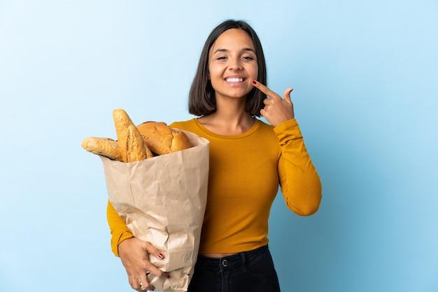 Молодая латинская женщина покупая некоторые изолированные хлеба на сини давая большие пальцы руки вверх показывать