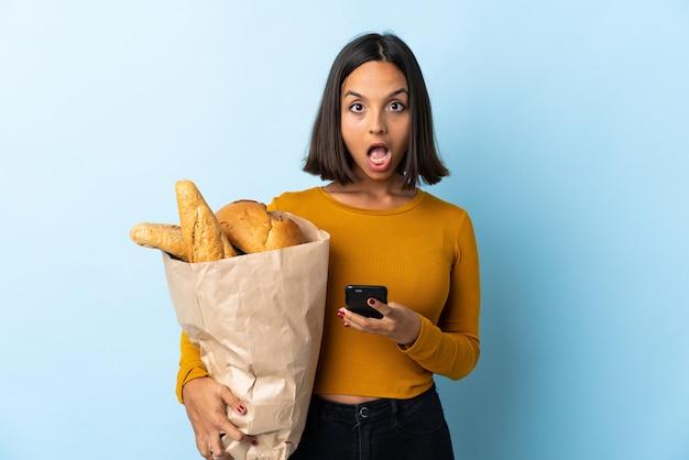 Удивленная молодая латинская женщина покупая некоторые хлебы на сини и посылая сообщение