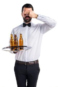 Официант с пивными бутылками на подносе, закрывающим глаза