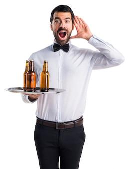 驚きのジェスチャーをしているトレイにビール瓶を入れたウェイター
