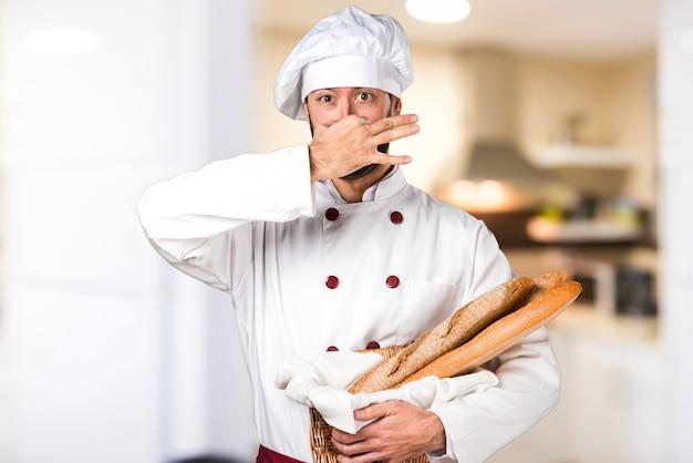 いくつかのパンを保持している若いパン屋は、キッチンの悪いジェスチャーを作る臭いを作る