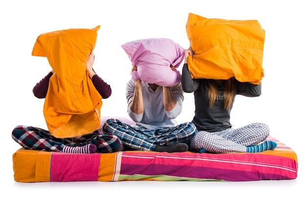Три друга на кровати, прячущиеся за подушками