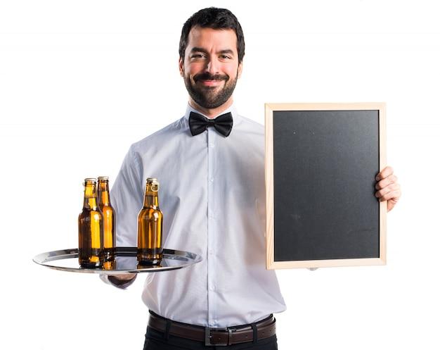 空のプラカードを持っているトレイにビール瓶を入れたウェイター