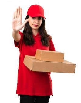 Молодая женщина доставки делает знак остановки