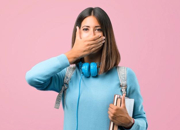 Молодая студентка девушка с синим свитером и наушники, охватывающих рот руками.