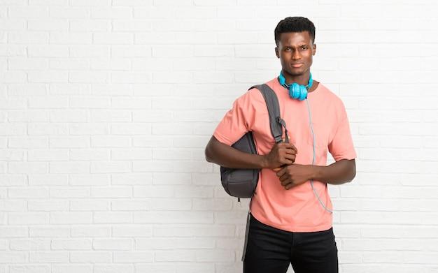 悲しい、うつ病の表現を持つ若いアフロアメリカ人の男子学生。深刻なジェスチャー