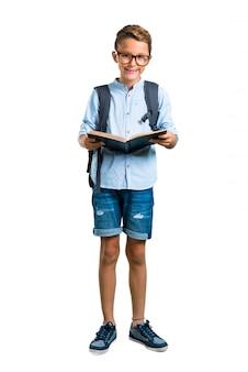 バックパックと本を持っている眼鏡を持つ学生の子供の全身。学校に戻る