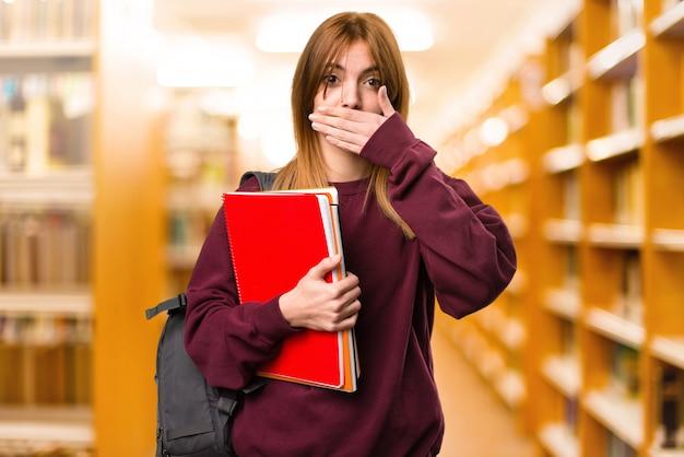 Студентка закрывает рот на фоне фокуса. обратно в школу