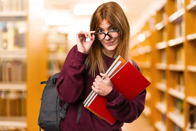 無焦点の背景に眼鏡を持つ学生の女性。学校に戻る