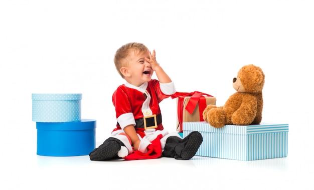 Очаровательный маленький ребенок, одетый как санта-клаус на рождественские вечеринки
