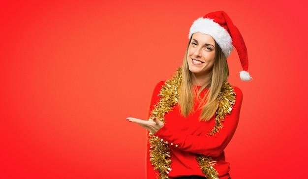 見るときにアイデアを提示するクリスマスの休日のために服を着せられたブロンドの女性