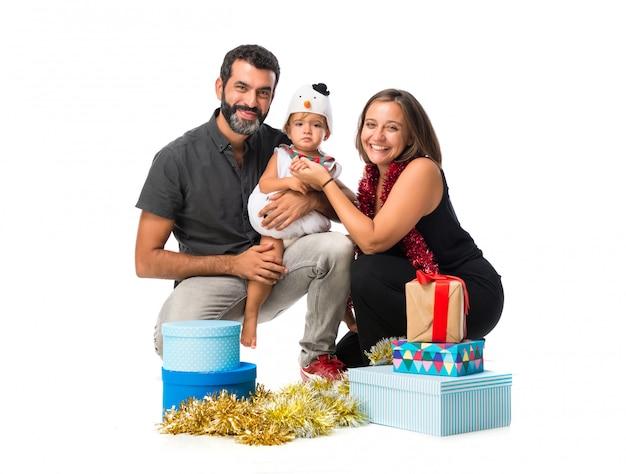 孤独な白い背景にクリスマスパーティーで両親と愛らしい小さな赤ちゃん
