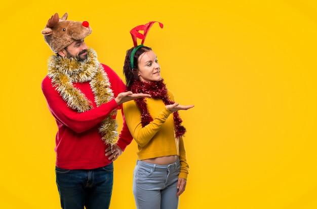 アイデアを提示するクリスマスの休日のために服を着たカップル