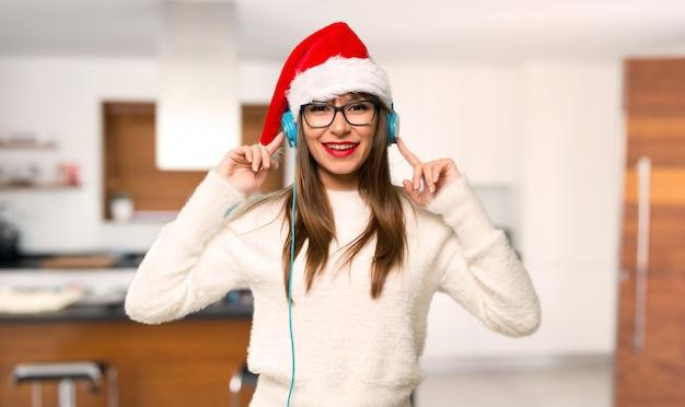 家庭でヘッドフォンで音楽を聴くクリスマス休暇を祝う少女