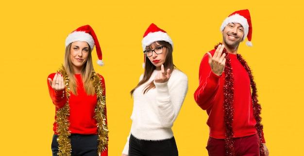人々のグループブロンドの女性はクリスマスの休日のプレゼンテーションのために服を着た