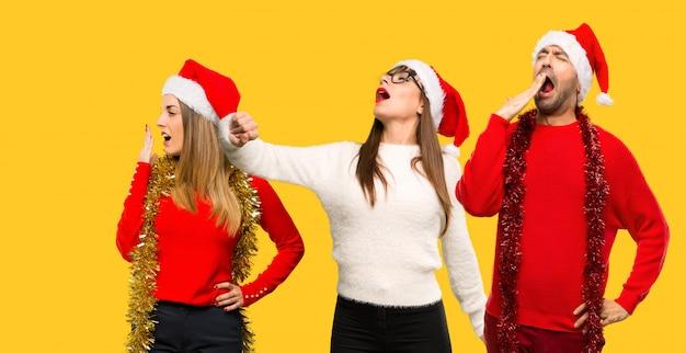 人々のグループブロンドの女性は夜を過ごすクリスマス休暇のために服を着た