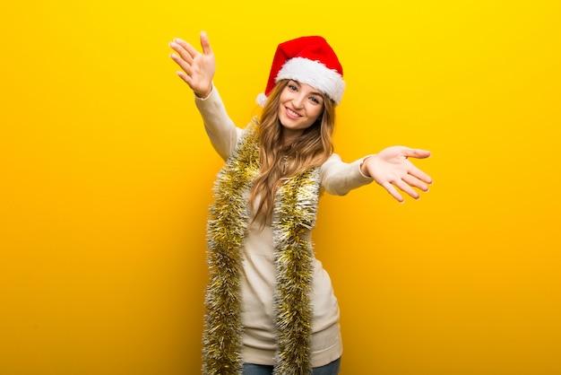 黄色の背景にクリスマスの休日を祝う女の子