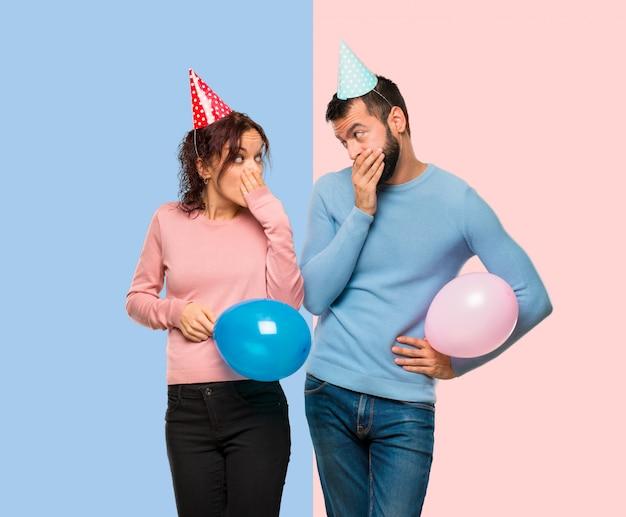 風船と誕生日の帽子を持つカップルは、何かを言って手で口を覆っている